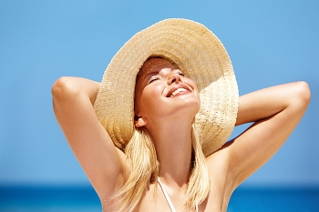 A blond girl wearing a hat under the beautiful sun