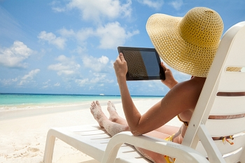 Woman having fun with her tablet by the sea