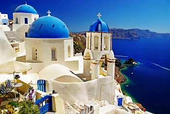View of white-cubed houses with blue domes backdropped by the blue sea and the caldera view on the Greek island of Santorini