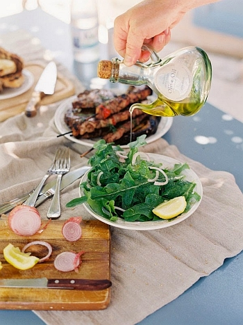Puring olive oil on Greek dishes