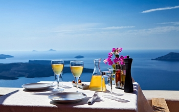 Table of glasses of wine and view of the caldera and the vast blue sea on Santorini island