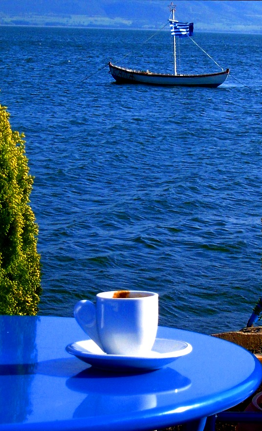 Greek coffee on a table backdropped by the infinite blue sea