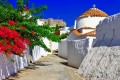 Picturesque alley with flowers and white washed buildings, Patmos island